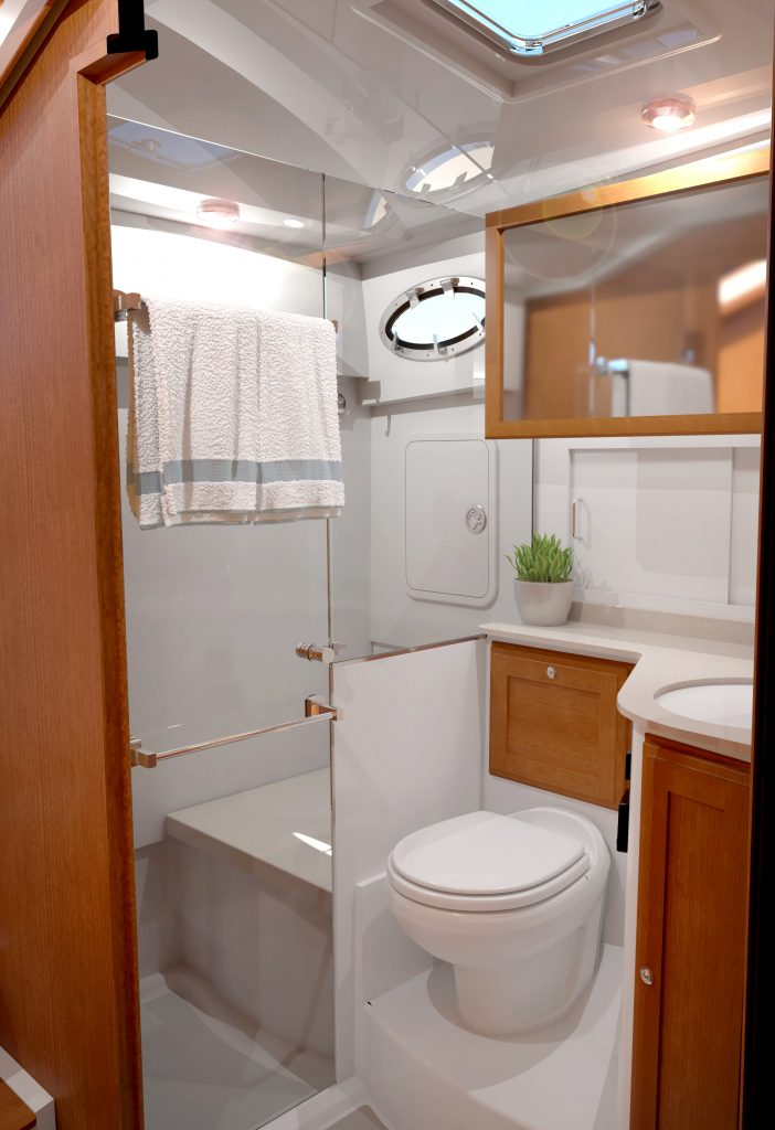 A computer rendering of the Back Cove 372 head unit, as laid out from the door. To the right of the image is the sink (cut off by the edge of the door frame), left of the sink and in the center of the image is the toilet (lower) with a section of the large over-sink mirror shown above. To the left-hand side of the image is a glass shower door with towel rack, and stall shower with a bench are shown through the door.