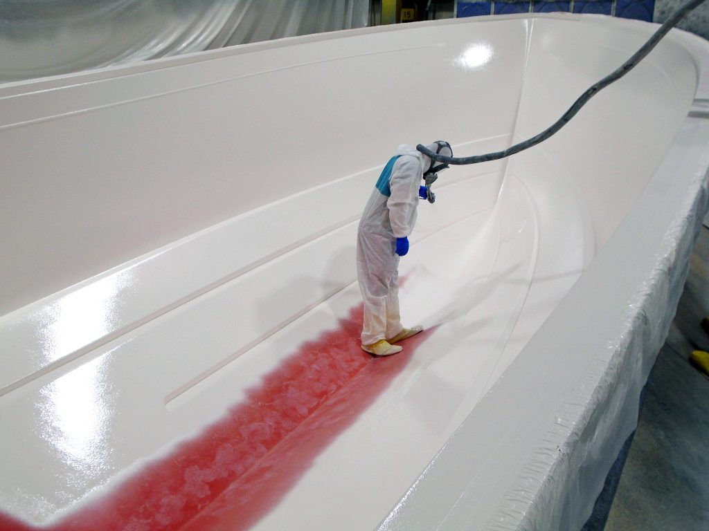 Image depicts a man dressed in a white suit (like a hazmat suit) connected to tubes and wearing a respirator. The man is standing inside a hull mold an spraying white gelcoat on the orange mold.