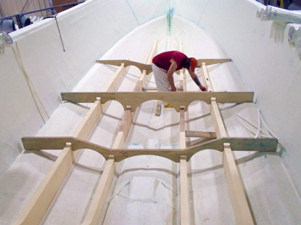 Photo of a man (center) installing long foam beams in the bottom of a hull. He is using wooden templates to ensure accurate spacing.