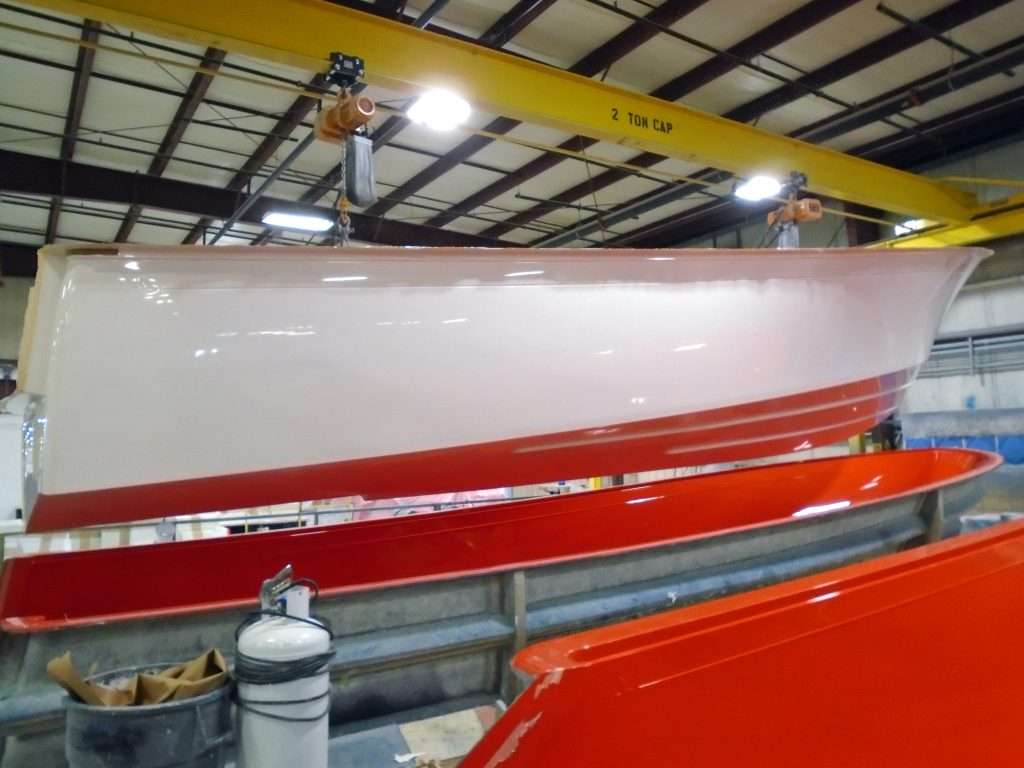 Photo shows a completed white boat hull as it is being lifted from the mold (orange) by two overhead winches. In the image, the hull is suspended several feet above the mold.