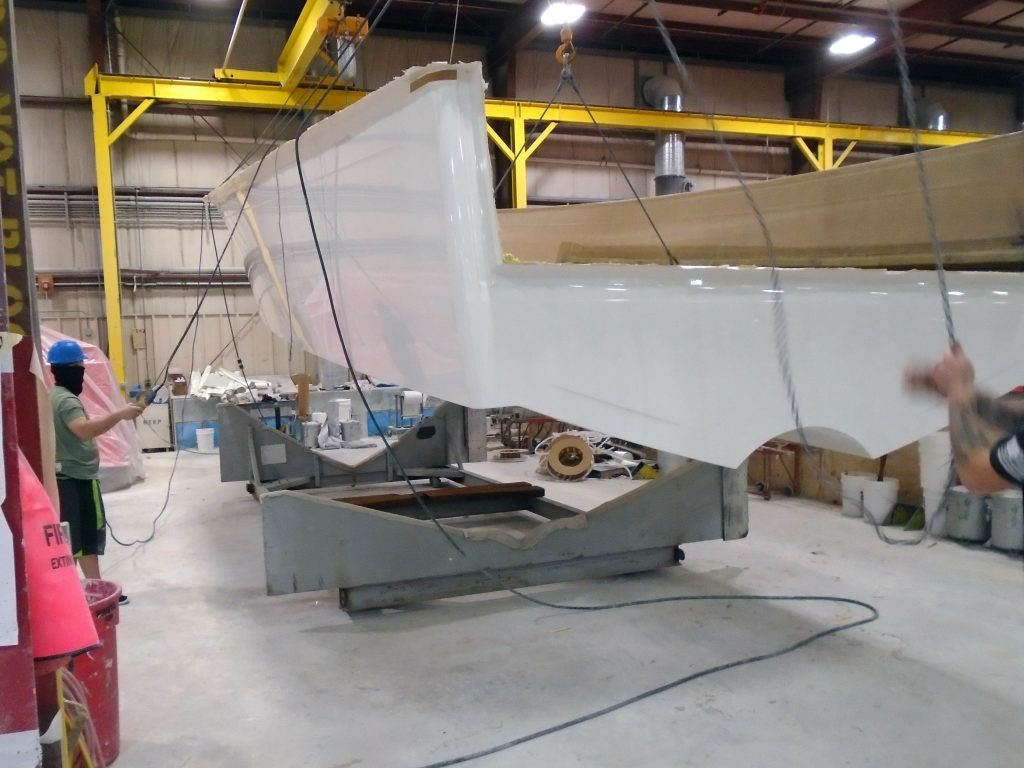 Photo - two workers (one to the left and one to the right) handle chains and switches to lower a white boat hull into a grey holder or rest (called a cradle) that sits on a grey cement floor.