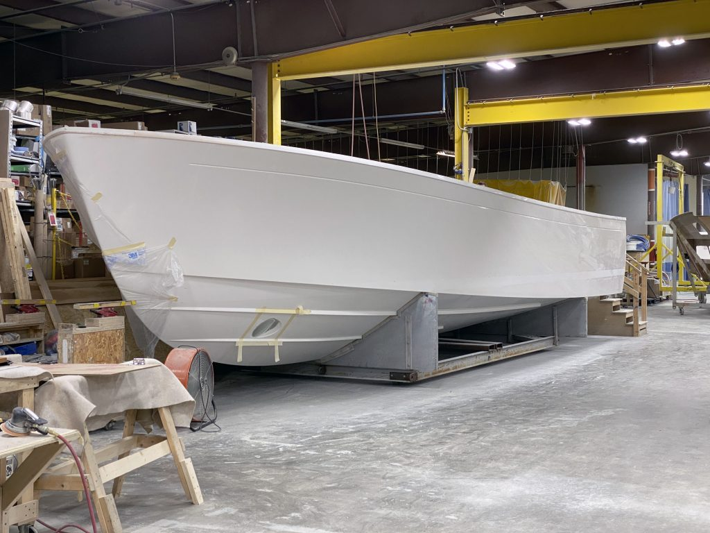 Photograph - depicts a white boat hull resting on a cradle in profile. The background shows a jumble of tools and construction materials.