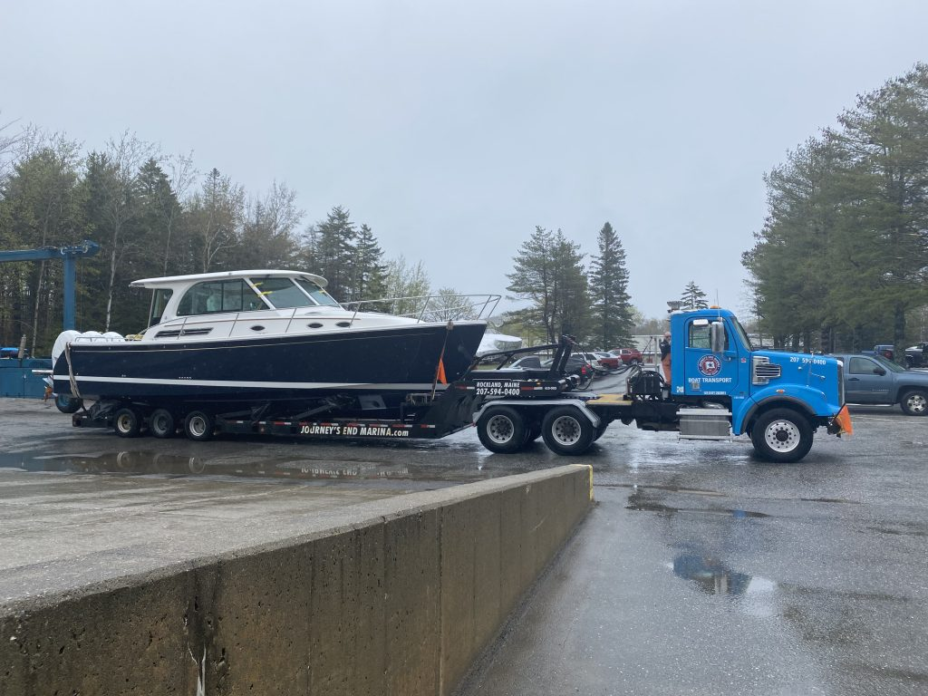 A truck sits in a parking lot, it's pulling a trailer on which a boat sits.